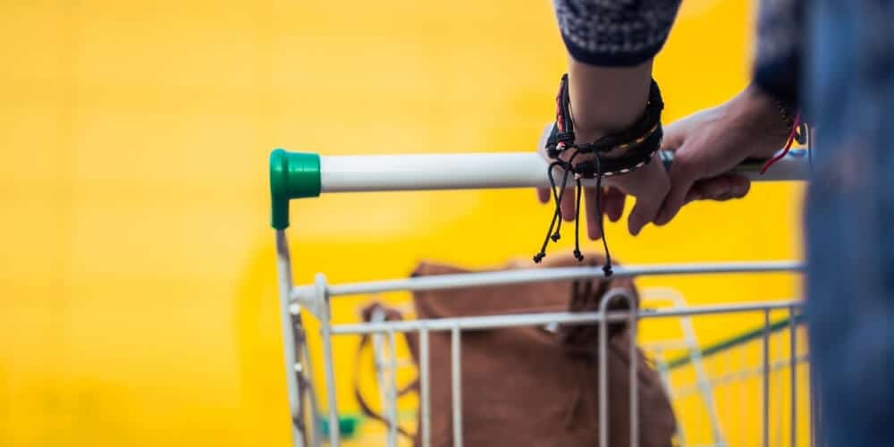 woman pushing shopping cart-save money on groceries without coupons