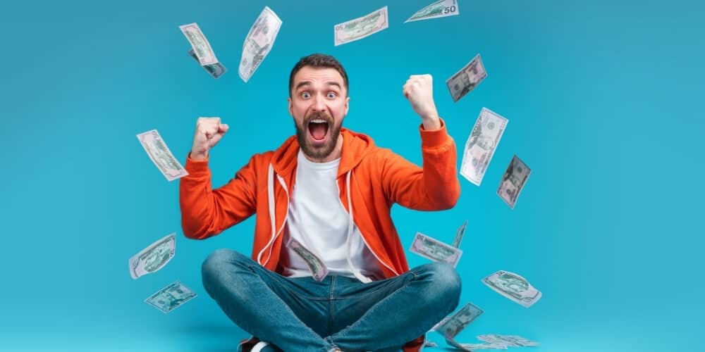 happy man sitting on ground surrounded by floating cash
