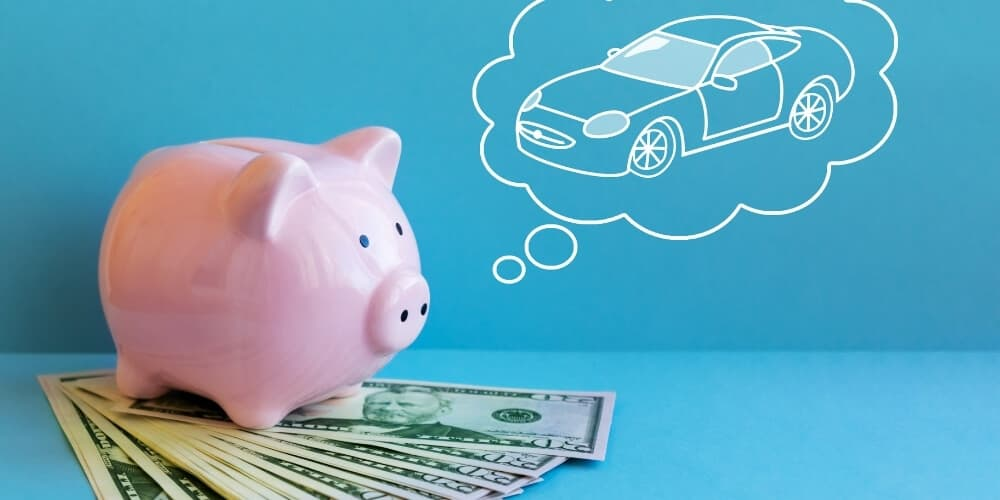 piggy bank on stack of money dreaming of a car-best frugal living tips