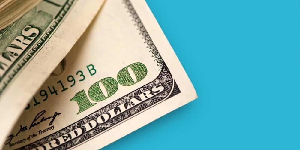100 dollar bills on teal background-best frugal living tips