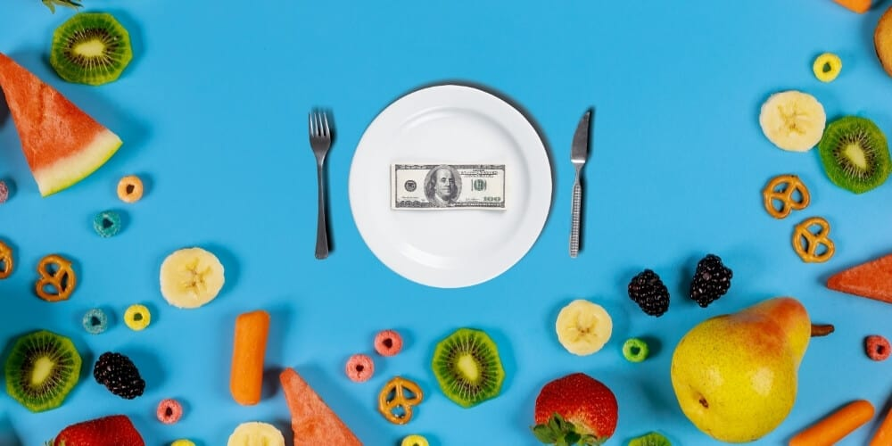 white plate with $100 bill surrounded by food on blue background-best frugal living tips