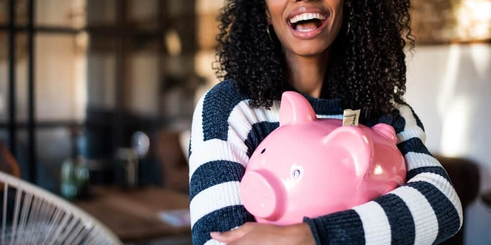 happy woman hugging piggy bank-why is budgeting so important