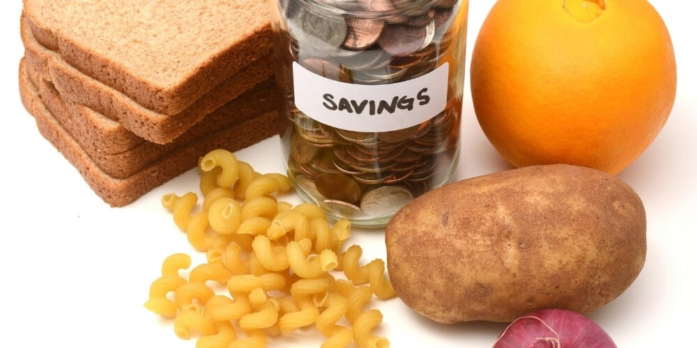 best cheap foods to buy when broke-jar of coins on table surrounded by food