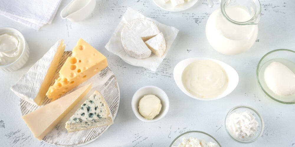 best cheap foods to buy when broke-milk and cheeses on white table top