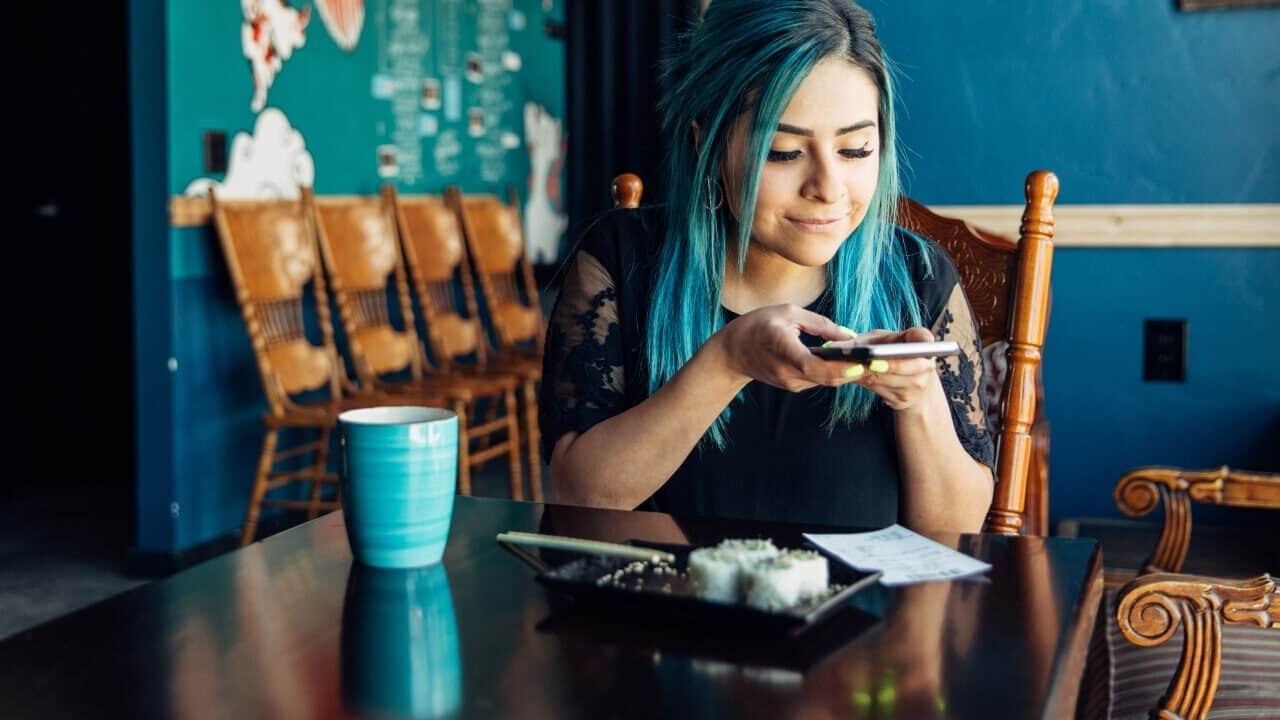 cheap eats near me-woman sitting at table in restaurant preparing to pay bill